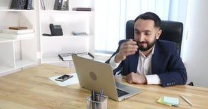Un sittingin heureux d'homme d'affaires son bureau fonctionnant à son ordinateur clips vidéos