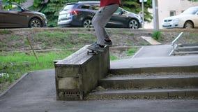 Un skater adulto que ama su afición joven salta en el encintado en las escaleras para realizar un resbalón en almacen de metraje de vídeo