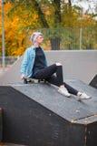 Un skater de la mujer se sienta en una rampa en un parque del patín Fotos de archivo