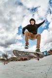 Un skater joven hace Wallie en un skatepark, saltando en un monopatín en el aire con un golpe Imagenes de archivo