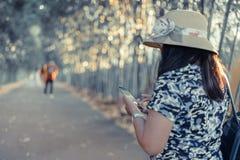 Un smartphone d'utilisation de femme pour des affaires pendant le voyage dans GA en bambou photographie stock
