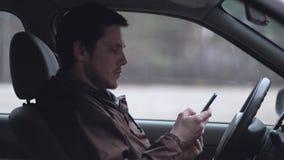 Un smartphone d'utilisation de jeune homme, se reposant dans la cabine de la voiture banque de vidéos
