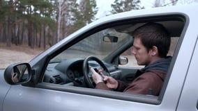 Un smartphone d'utilisation de jeune homme, se reposant dans la cabine de la voiture clips vidéos