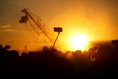 Un smartphone en un uno mismo-palillo, un festival de música del verano en la puesta del sol Foto de archivo libre de regalías