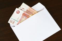 Un sobre blanco con un paquete de ruso cinco mil mentiras de los billetes de banco de la rublo en una tabla oscura Fotos de archivo