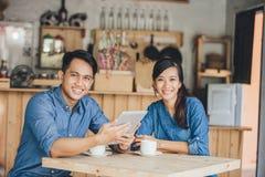 Un socio commerciale di due giovani che per mezzo insieme della compressa Immagini Stock