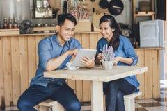 Un socio commerciale di due giovani che per mezzo insieme della compressa Immagine Stock