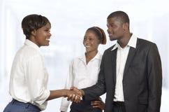 Un socio commerciale di tre Africani stringe le mani alla riunione Fotografia Stock Libera da Diritti