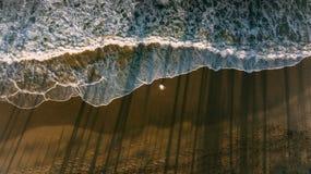 Un soggiorno degli uomini sulla spiaggia Wave e riflessione dell'ombra dalle palme scuro immagine stock
