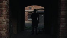 Un soldado alemán que camina lentamente en un túnel oscuro de un edificio de ladrillo rojo antiguo Reconstrucción de la Segunda G metrajes