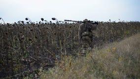 Un soldado camina a lo largo del campo En el hombro de un rifle de francotirador Girasoles secados Otoño 2016 La guerra en Ucrani almacen de video