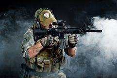 Un soldado en el humo después de la explosión Foto de archivo