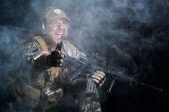 Un soldado en el humo después de la explosión Fotografía de archivo