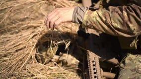 Un soldado en un explorador de la guerra pone la hierba seca en casco del camuflaje para crear camuflaje en el bosque metrajes