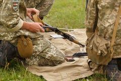 Un soldado monta un Kalashnikov del rifle de asalto imágenes de archivo libres de regalías
