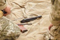 Un soldado monta un Kalashnikov del rifle de asalto imagen de archivo libre de regalías