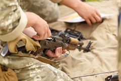 Un soldado monta un Kalashnikov del rifle de asalto imagen de archivo