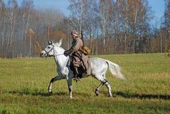 Un soldado-reenactor monta un caballo blanco Fotografía de archivo