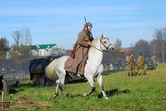 Un soldado-reenactor monta un caballo blanco Imagen de archivo libre de regalías