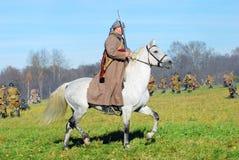 Un soldado-reenactor monta un caballo blanco Fotografía de archivo libre de regalías