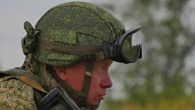Un soldado ruso con una ametralladora en un tiroteo militar de la gama de leña en una blanco FullHD almacen de video