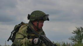 Un soldado ruso con una ametralladora en un tiroteo militar de la gama de leña en una blanco HD metrajes