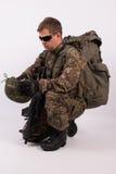 Un soldado se agachó en uniforme Imágenes de archivo libres de regalías