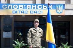 Un soldado se coloca cerca de una bandera ucraniana Fotos de archivo libres de regalías