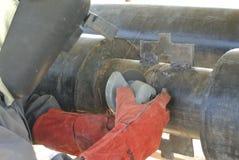 Un soldador autorizado está utilizando la amoladora Fotografía de archivo
