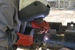 Un soldador que suelda con autógena un tubo Imágenes de archivo libres de regalías