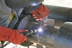 Un soldador que suelda con autógena un tubo Imagen de archivo