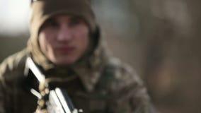Un soldato con una pistola AK-47 che prepara infornare stock footage