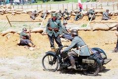 Un soldato guida una motocicletta Immagine Stock
