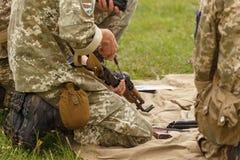 Un soldato monta un Kalashnikov del fucile di assalto immagine stock