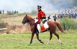 Un soldato monta un cavallo marrone. Immagine Stock