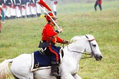 Un soldato-reenactor ha vestito nei giri di rosso un cavallo bianco Immagini Stock Libere da Diritti