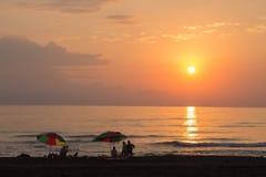 Un soleil de coucher du soleil au-dessus de l'océan avec des personnes appréciant la vue Les personnes de silhouettes au fond de  Image stock