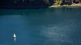 Un solo barco de vela en un lago Fotografía de archivo