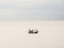 Un solo barco del pescador en el mar Imagenes de archivo