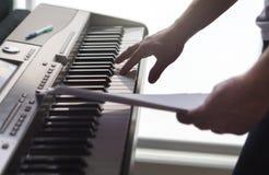 Un solo finger que pulsa tecla en piano Fotos de archivo