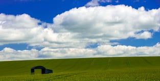 Un solo granero con las nubes blancas en el cielo azul Fotos de archivo