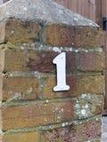 Un solo número de matrícula blanco de 1 exterior en la pared de la casa de la pared Foto de archivo libre de regalías