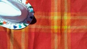 Un sombrero blanco en la tela escocesa roja brillante Imagen de archivo