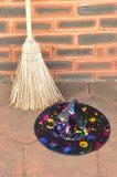Un sombrero colorido de las brujas y una escoba Imagenes de archivo