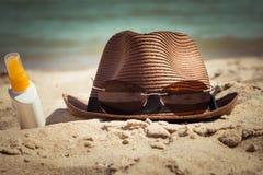 Un sombrero con gafas de sol y una botella de loción de la protección solar Fotos de archivo libres de regalías