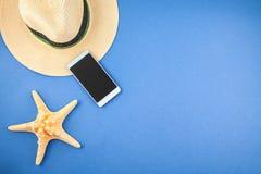 Un sombrero de paja, un teléfono y una estrella de mar en un fondo azul Copyspace de la visión superior foto de archivo