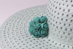 Un sombrero femenino de ala ancha es verde claro, adornado con las flores hechas en casa Flores artificiales bajo la forma de ros Fotografía de archivo