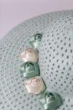 Un sombrero femenino de ala ancha es verde claro, adornado con las flores hechas en casa Flores de la tela bajo la forma de rosas Foto de archivo libre de regalías