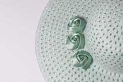 Un sombrero femenino de ala ancha es verde claro, adornado con las flores hechas en casa Flores de la tela bajo la forma de rosas Imagen de archivo