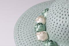 Un sombrero femenino de ala ancha es verde claro, adornado con las flores hechas en casa Flores de la tela bajo la forma de rosas Imagen de archivo libre de regalías